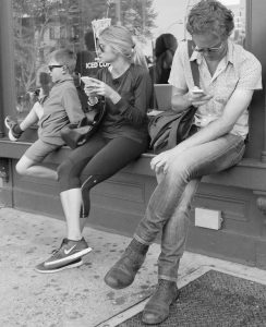 Parents looking at cell phones on Sheridan Square near Stabrucks in Greenwich Village with young boy.